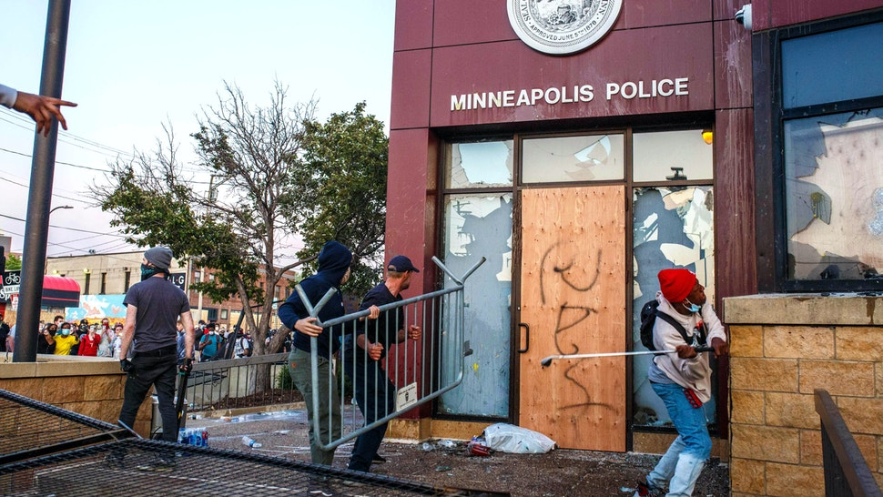 Protesters use a barricade to try and break the windows of the Third Police Precinct on May 28, 2020 in Minneapolis, Minnesota, during a protest over the death of George Floyd, an unarmed black man, died after a police officer kneeled on his neck for several minutes. - Authorities in Minneapolis and its sister city St. Paul got reinforcements from the National Guard on May 28 as they girded for fresh protests and violence over the shocking police killing of a handcuffed black man. Three days after a policeman was filmed holding his knee to George Floyd's neck for more than five minutes until he went limp, outrage continued to spread over the latest example of police mistreatment of African Americans.