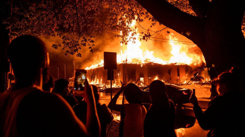 """People look on as a construction site burns in a large fire near the Third Police Precinct on May 27, 2020 in Minneapolis, Minnesota. A number of businesses and homes were damaged as the area has become the site of an ongoing protest after the police killing of George Floyd. Four Minneapolis police officers have been fired after a video taken by a bystander was posted on social media showing Floyd's neck being pinned to the ground by an officer as he repeatedly said, """"I can't breathe"""". Floyd was later pronounced dead while in police custody after being transported to Hennepin County Medical Center. (Photo by Stephen Maturen/Getty Images)"""