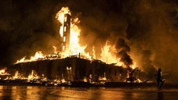 """MINNEAPOLIS, MN - MAY 27: A construction site burns in a large fire near the Third Police Precinct on May 27, 2020 in Minneapolis, Minnesota. A number of businesses and homes were damaged as the area has become the site of an ongoing protest after the police killing of George Floyd. Four Minneapolis police officers have been fired after a video taken by a bystander was posted on social media showing Floyd's neck being pinned to the ground by an officer as he repeatedly said, """"I can't breathe"""". Floyd was later pronounced dead while in police custody after being transported to Hennepin County Medical Center."""
