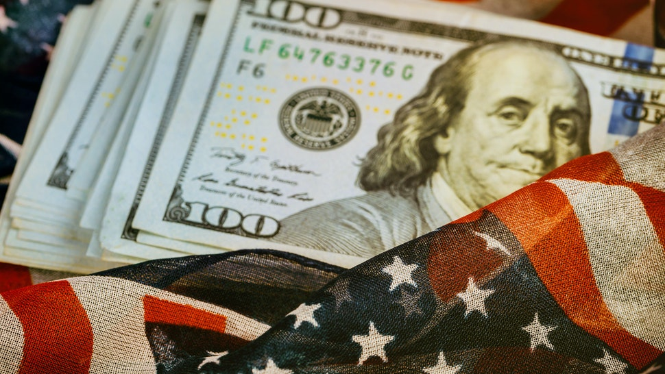 One hundred dollar bill with an American flag background