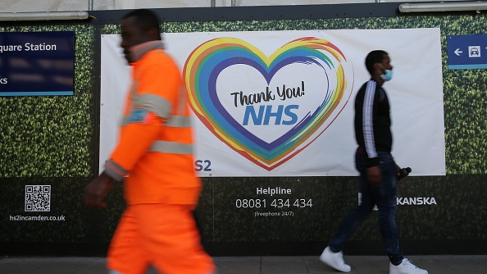 Two men walk past a sign thanking members of the NHS who continue to work during the COVID-19 outbreak at the HS2 building site near Euston in London on May 6, 2020 as life continues under a nationwide lockdown imposed to slow the spread of the novel coronavirus. - Cross-Channel train operator Eurostar on May 2 said face masks covering the mouth and nose would be compulsory on services between London, Paris and Brussels from May 4. Britain's death toll from the coronavirus has topped 32,000, according to an updated official count released May 5, pushing the country past Italy to become the second-most impacted after the United States.