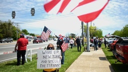 """Protestors wave US flags as they attend an """"Open New York"""" Rally on May 14, 2020 in Commack, on Long Island, New York. (Photo by Johannes EISELE / AFP)"""