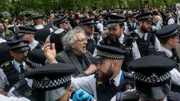 LONDON, ENGLAND - MAY 16: Piers Corbyn (brother of former Labour leader Jeremy Corbyn) is arrested as conspiracy theorists gather at Hyde Park Corner to defy the emergency legislation and protest their claim that the Coronavirus pandemic is part of a secret conspiracy on May 16, 2020 in London, United Kingdom. The prime minister has announced the general contours of a phased exit from the current lockdown, adopted nearly two months ago in an effort curb the spread of Covid-19.