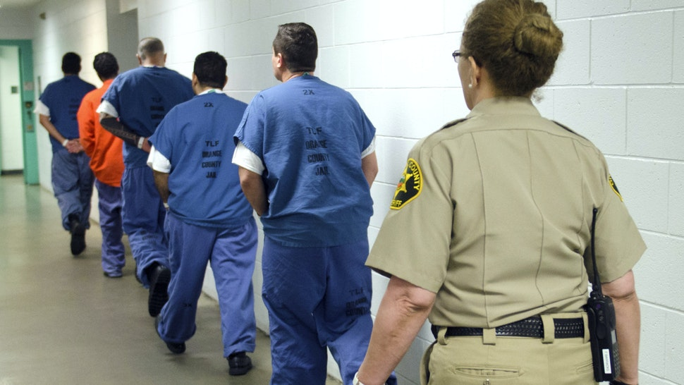 ORANGE, CA - MARCH 14: Detainees are escorted down a hall in at the Theo Lacy Facility in Orange, California, on Tuesday, March 14, 2017. The Orange County sheriff conducted a media tour of the jail that included the intake area, the kitchen, an isolation unit and a modular holding area.