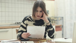 Stressed young woman makes calculations on taxes to be paid