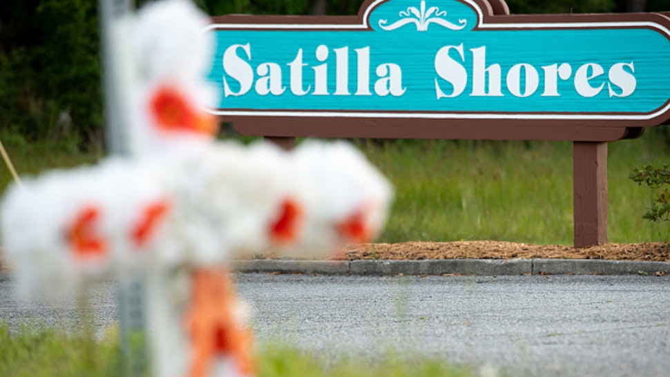 """BRUNSWICK, GA - MAY 06: A cross with flowers and a letter """"A"""" sits at the entrance to the Satilla Shores neighborhood where Ahmaud Arbery was shot and killed on May 6, 2020 in Brunswick, Georgia. Attorneys for Arbery released a video that appears to show the 25-year-old being gunned down while jogging during a confrontation with an armed father and son on February 23."""