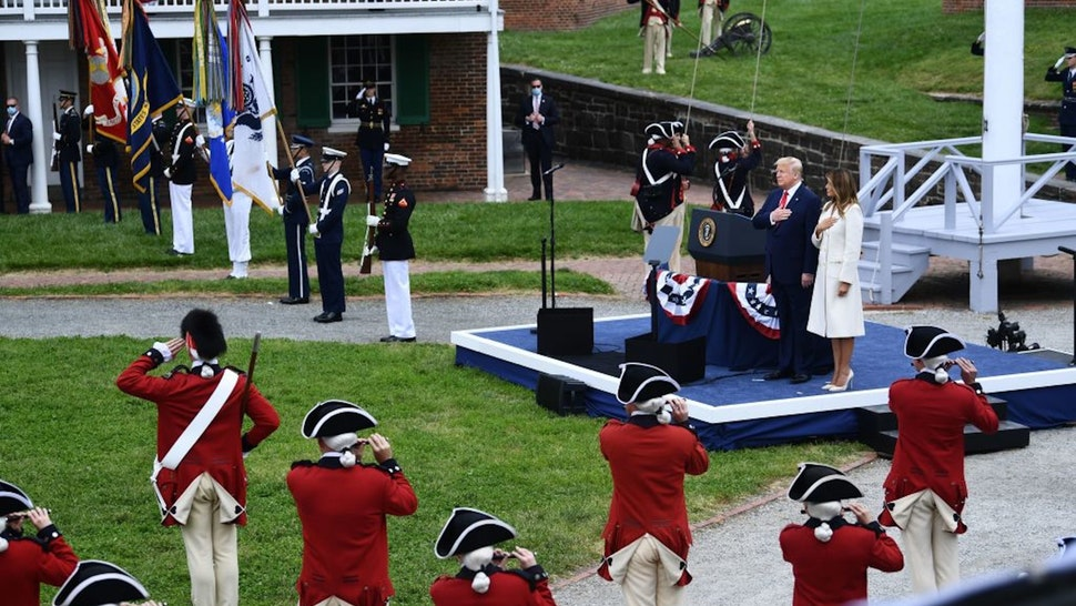 US President Donald Trump(C) and First Lady Melania Trump put their hands on their heart as they participate in a Memorial Day Ceremony at Fort McHenry National Monument and Historic Shrine on May 25, 2020 in Baltimore, Maryland. (Photo by Brendan Smialowski / AFP)