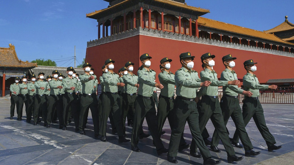 BEIJING, CHINA - MAY 20: Soldiers of the People's Liberation Army's Honour Guard Battalion march outside the Forbidden City, near Tiananmen Square, on May 20, 2020 in Beijing, China. China's government will open its annual weeklong meetings known as the 'two sessions' at the Great Hall of the People on May 21st. They were delayed in March due to the COVID-19 pandemic. After decades of growth, officials recently said China's economy had shrunk in the latest quarter due to the impact of the coronavirus epidemic. The slump in the worlds second largest economy is regarded as a sign of difficult times ahead for the global economy. While industrial sectors in China are showing signs of reviving production, a majority of private companies are operating at only 50% capacity, according to analysts. With the pandemic hitting hard across the world, officially the number of coronavirus cases in China is dwindling, ever since the government imposed sweeping measures to keep the disease from spreading. Officials believe the worst appears to be over in China, though there are concerns of another wave of infections as the government attempts to reboot the worlds second largest economy. Since January, China has recorded more than 82,000 cases of COVID-19 and at least 4000 deaths, mostly in and around the city of Wuhan, in central Hubei province, where the outbreak first started.