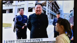 TOPSHOT - A woman walks past a television news screen showing a picture of North Korean leader Kim Jong Un attending a ceremony to mark the completion of Sunchon phosphatic fertiliser factory, at a railway station in Seoul on May 2, 2020. - North Korea's Kim Jong Un has made his first public appearance in nearly three weeks, state media reported on May 2, following intense speculation that the leader of the nuclear-armed nation was seriously ill or possibly dead. (Photo by Jung Yeon-je / AFP) (Photo by