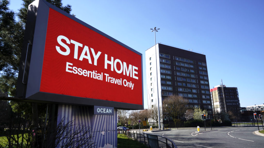 MANCHESTER, - MARCH 26: A giant television over the A57 Motorway urges people to stay home on March 26, 2020 in Manchester, England. British Prime Minister, Boris Johnson, announced strict lockdown measures urging people to stay at home and only leave the house for basic food shopping, exercise once a day and essential travel to and from work. The Coronavirus (COVID-19) pandemic has spread to at least 182 countries, claiming over 10,000 lives and infecting hundreds of thousands more.