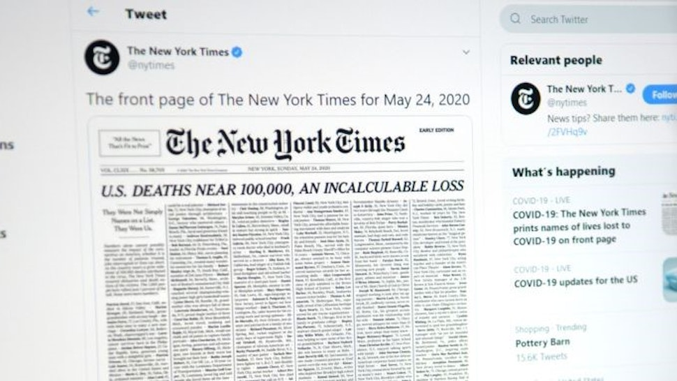 This picture taken on May 23, 2020, in Los Angeles, California, shows a woman looking at a computer screen with a tweet by the New York Times newspaper account showing the early edition front page of May 24, 2020, with a list of 1,000 names printed on it, that represents 1% of the lives lost due to the novel coronavirus pandemic, COVID-19, in the US. (Photo by Agustin PAULLIER / AFP) (Photo by