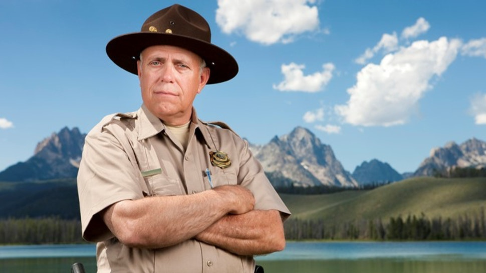 A mature male park ranger (or police officer) standing in front of a beautiful scenic backdrop of tall mountains and a mirror lake.