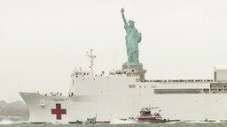 NEW YORK, UNITED STATES - 2020/04/30: On a gloomy rainy day USNS Comfort hospital ship leaves New York City in front of Statue of Liberty after treating some patients during COVID-19 pandemic. (Photo by