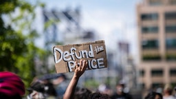 "MANHATTAN, NY - JUNE 19: A protester holds up a homemade sign that says, ""Defund the Police"" with the Manhattan Bridge behind them as they perform a peaceful protest walk across the Brooklyn Bridge."