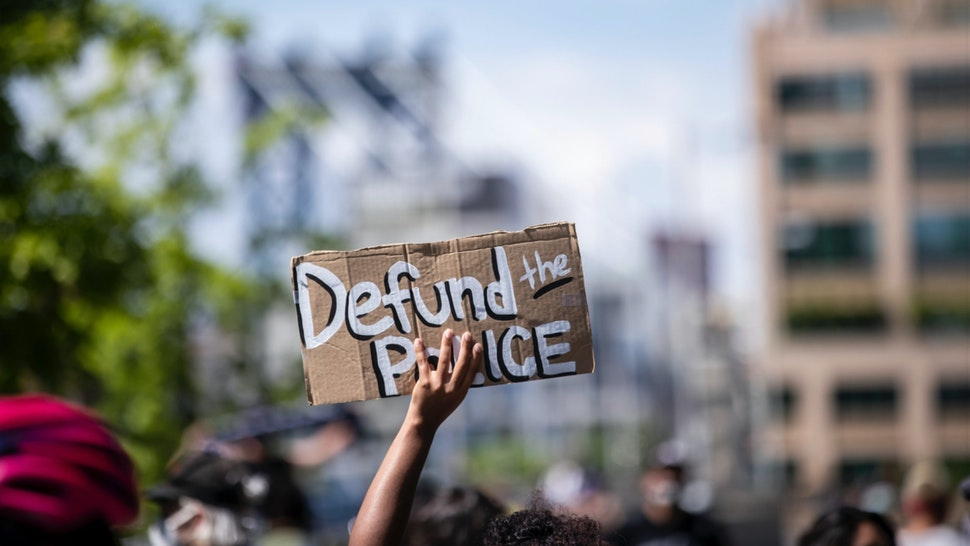 """MANHATTAN, NY - JUNE 19: A protester holds up a homemade sign that says, """"Defund the Police"""" with the Manhattan Bridge behind them as they perform a peaceful protest walk across the Brooklyn Bridge."""
