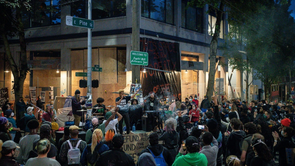 """A band plays a free show in front of the Seattle Police Departments East Precinct in the so-called """"Capitol Hill Autonomous Zone"""" on June 10, 2020 in Seattle, Washington."""