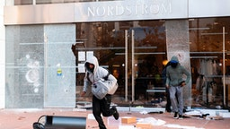 People are seen looting stores at the Grove shopping center in the Fairfax District of Los Angeles on May 30, 2020 following a protest against the death of George Floyd, an unarmed black man who died while while being arrested and pinned to the ground by the knee of a Minneapolis police officer.