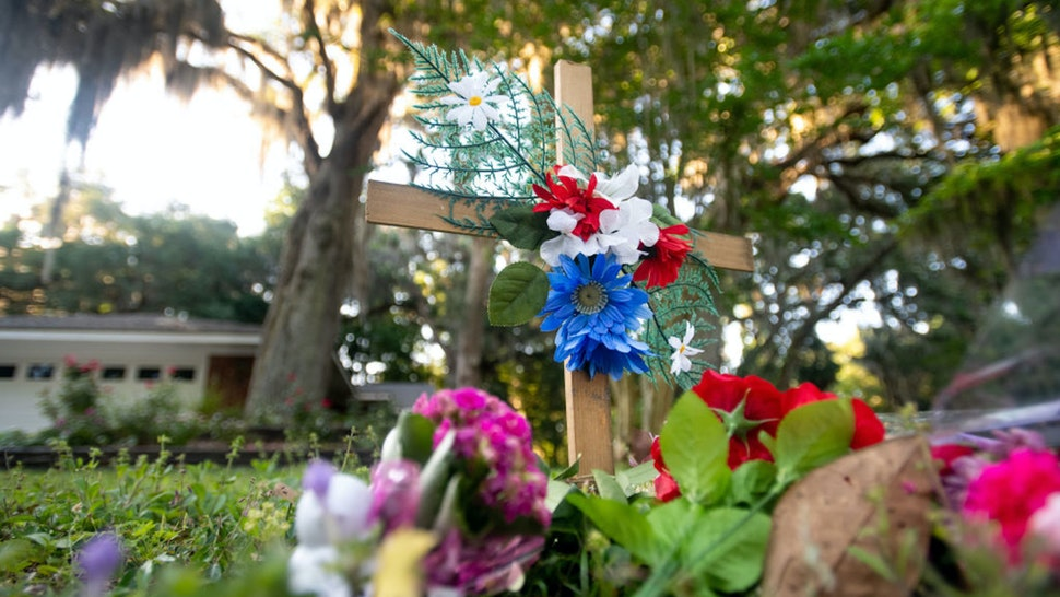 BRUNSWICK, GA - MAY 07: A cross with flowers sits near the intersection of Satilla Rd. and Holmes Rd. in the Satilla Shores neighborhood where Ahmaud Arbery was shot and killed May 7, 2020 in Brunswick, Georgia. Arbery was shot during a confrontation with an armed father and son on Feb. 23.