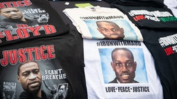 BRUNSWICK, GA - JUNE 04: T-shirts memorializing George Floyd and Ahmaud Arbery are displayed for sale on a car hood outside the Glynn County courthouse during a court appearance by Gregory and Travis McMichael, two suspects in the fatal shooting of Ahmaud Arbery, on June 4, 2020 in Brunswick, Georgia. Arbery was killed on February 23.