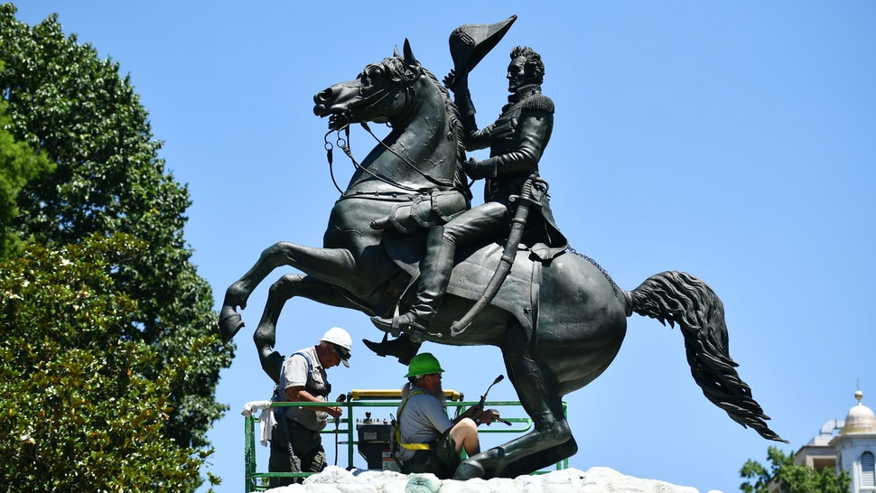 Workers clean a statue of Andrew Jackson in the recently reopened Lafayette Square near the White House, in Washington, DC on June 12, 2020.
