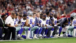Members of the Dallas Cowboys link arms and kneel during the National Anthem before the start of the NFL game against the Arizona Cardinals at the University of Phoenix Stadium on September 25, 2017 in Glendale, Arizona. (Photo by Christian Petersen/Getty Images)