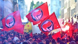 """Participants of the """"Revolutionary 1st of May Demonstration"""" light flares and wave flags of the left-wing, Anti-Fascist Antifa movement during May Day events on May 1, 2018 in Berlin."""