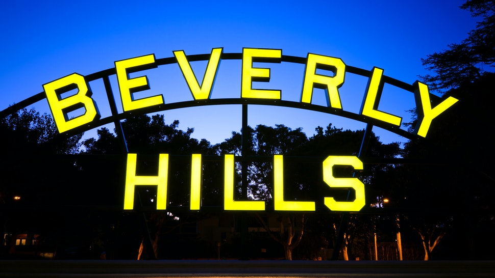 Beverly Hills sign located along Santa Monica Boulevard in Beverly Hills, CA at night.