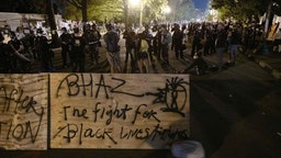 """Protesters confront police near a barricade they erected and marked with the sign """"Black House Autonomous Zone"""" in front of Lafayette Park near the White House, in Washington, DC on June 22, 2020. - A crowd of protestors tried to topple the statue of former US president General Andrew Jackson near the White House in the evening of June 22 as police responded with pepper spray to break up new demonstrations that erupted in Washington. (Photo by ROBERTO SCHMIDT / AFP)"""