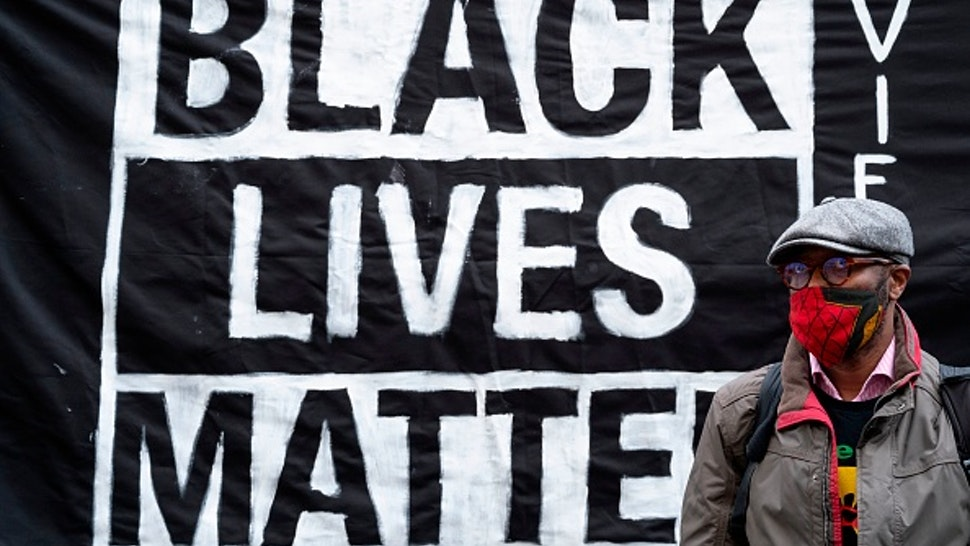 A protestor stands in front of a banner during a demonstration on June 5, 2020 outside the US embassy in Vienna, Austria, to show solidarity with the Black Lives Matter movement in the wake of the killing of George Floyd, an unarmed black man who died after a police officer knelt on his neck in Minneapolis. - Hundreds of mourners joined an emotional memorial service in Minneapolis for George Floyd, the black man killed by police last week.The police killing of George Floyd led to diverse protests calling for an end to violence towards African Americans, whom studies have found face an elevated risk of dying at the hands of law enforcement