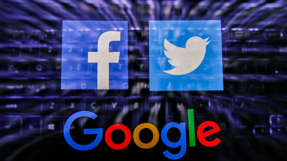 Facebook, Twitter and Google logos displayed on a phone screen and keyboard are seen in this multiple exposure illustration photo taken in Poland on June 14, 2020. European Commission officials said that Facebook, Twitter and Google should provide monthly fake news reports to prevent fake news about coronavirus pandemic. (Photo Illustration by Jakub Porzycki/NurPhoto via Getty Images)