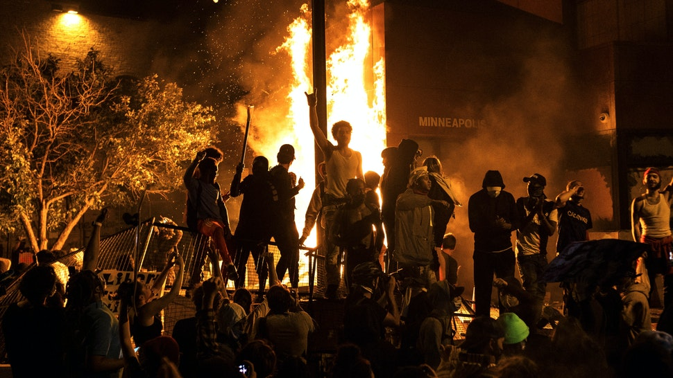 MINNEAPOLIS, MN - MAY 28: Protesters cheer as the Third Police Precinct burns behind them on May 28, 2020 in Minneapolis, Minnesota. As unrest continues after the death of George Floyd, police abandoned the precinct building, allowing protesters to set fire to it.