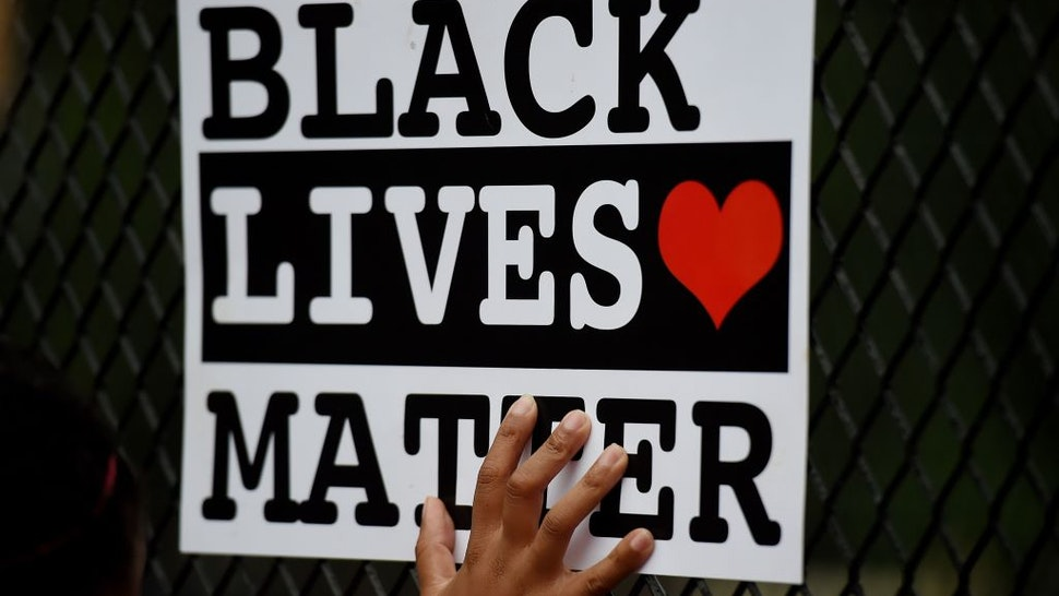 A protestor holds up a Black Lives Matter sign against a recently erected metal fence in front of Lafayette Square near the White House to keep protestors at bay on June 4, 2020 in Washington, DC. - On May 25, 2020, Floyd, a 46-year-old black man suspected of passing a counterfeit $20 bill, died in Minneapolis after Derek Chauvin, a white police officer, pressed his knee to Floyd's neck for almost nine minutes. (Photo by Olivier DOULIERY / AFP) (Photo by OLIVIER DOULIERY/AFP via Getty Images)