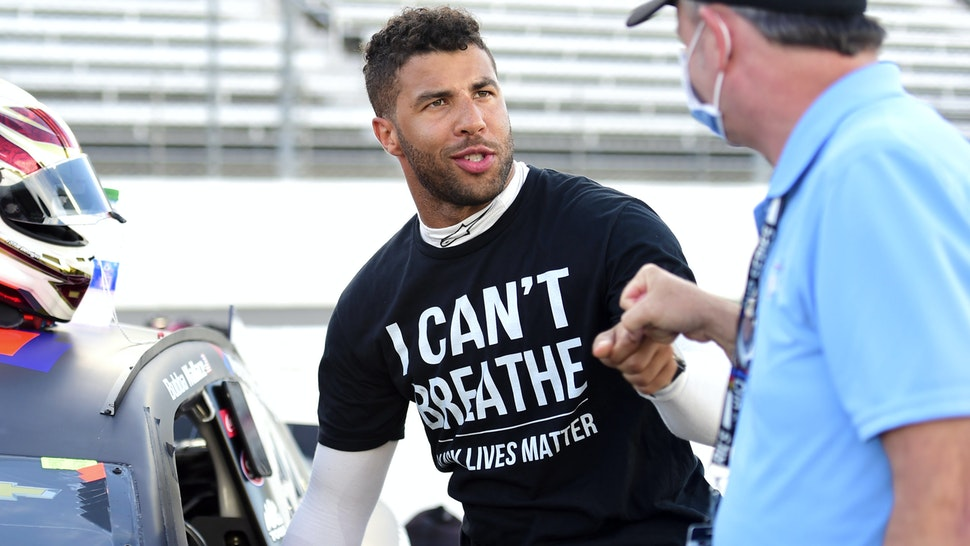 "MARTINSVILLE, VIRGINIA - JUNE 10: Bubba Wallace, driver of the #43 Richard Petty Motorsports Chevrolet, wears a ""I Can't Breathe - Black Lives Matter"" t-shirt under his fire suit in solidarity with protesters around the world taking to the streets after the death of George Floyd on May 25, and crew bump fist prior to the NASCAR Cup Series Blue-Emu Maximum Pain Relief 500 at Martinsville Speedway on June 10, 2020 in Martinsville, Virginia."