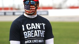 "HAMPTON, GEORGIA - JUNE 07: Bubba Wallace, driver of the #43 McDonald's Chevrolet, wears a ""I Can't Breathe - Black Lives Matter"" T-shirt under his fire suit in solidarity with protesters around the world taking to the streets after the death of George Floyd on May 25 while in the custody of Minneapolis, Minnesota police stands on the grid prior to the NASCAR Cup Series Folds of Honor QuikTrip 500 at Atlanta Motor Speedway on June 07, 2020 in Hampton, Georgia."