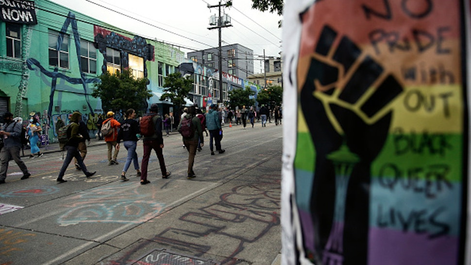 """A sign that reads """"no pride without Black Queer lives"""" is pictured as people walk in an area being called the Capitol Hill Autonomous Zone (CHAZ) located on streets reopened to pedestrians after the Seattle Police Department's East Precinct was vacated in Seattle, Washington on June 12, 2020. - Seattle's mayor told Donald Trump to """"Go back to your bunker"""" June 11, escalating a spat after the president threatened to intervene over a police-free autonomous zone protesters have set up in the western US city."""