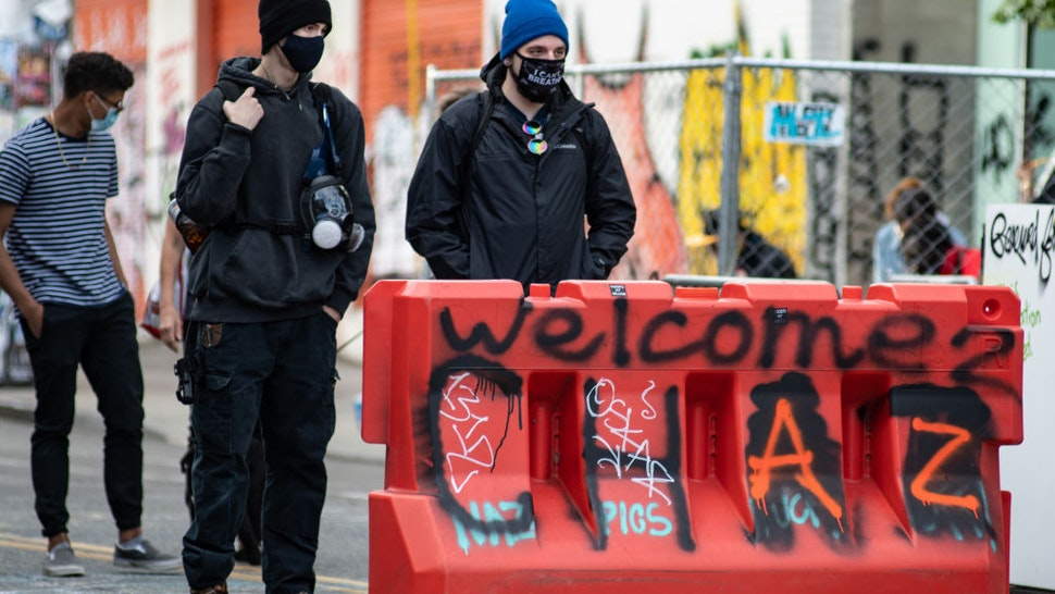 Two people stand at an entrance to the √¢Capitol Hill Organized Protest√¢ formerly known as the √¢Capitol Hill Autonomous Zone√¢ in Seattle, Washington on June 14, 2020. The √¢Capitol Hill Organized Protest√¢ was formed after Seattle Police abandoned its East Precinct during protests against police brutality and the death of George Floyd, an unarmed black man who died after being pinned down by a white police officer in Minneapolis, Minnesota, United States on May 25, 2020. (Photo by Noah Riffe/Anadolu Agency via Getty Images)