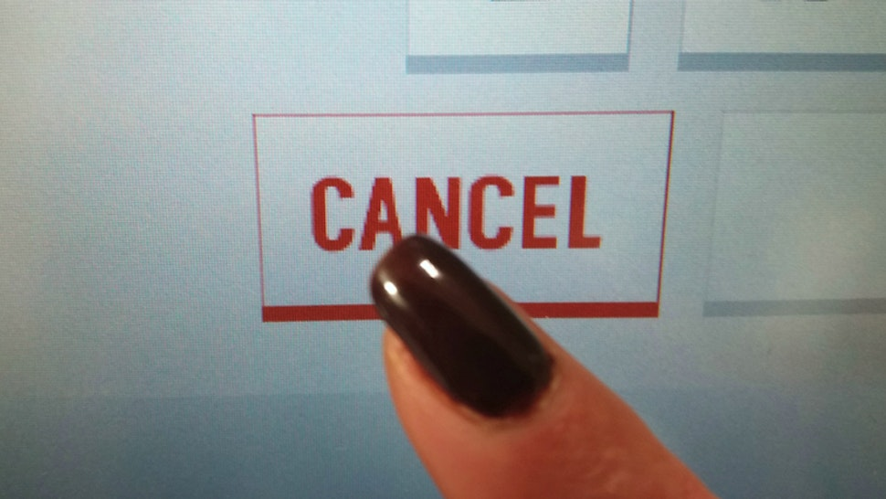 Finger clicks the word CANCEL on the touch screen
