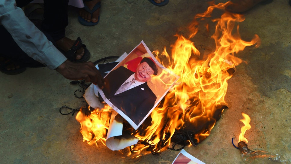 Members of the non-governmental organisation MADADGAAR PARIVAR, burn a poster of Chinese President Xi Jinping along with Chinese items as they protest against the killing of the three Indian soldiers by Chinese troops, in Ahmedabad on June 16, 2020. - Three Indian soldiers were killed in a violent face-off on the Chinese border, the Indian army said June 16, following weeks of rising tensions and the deployment of thousands of extra troops from both sides.