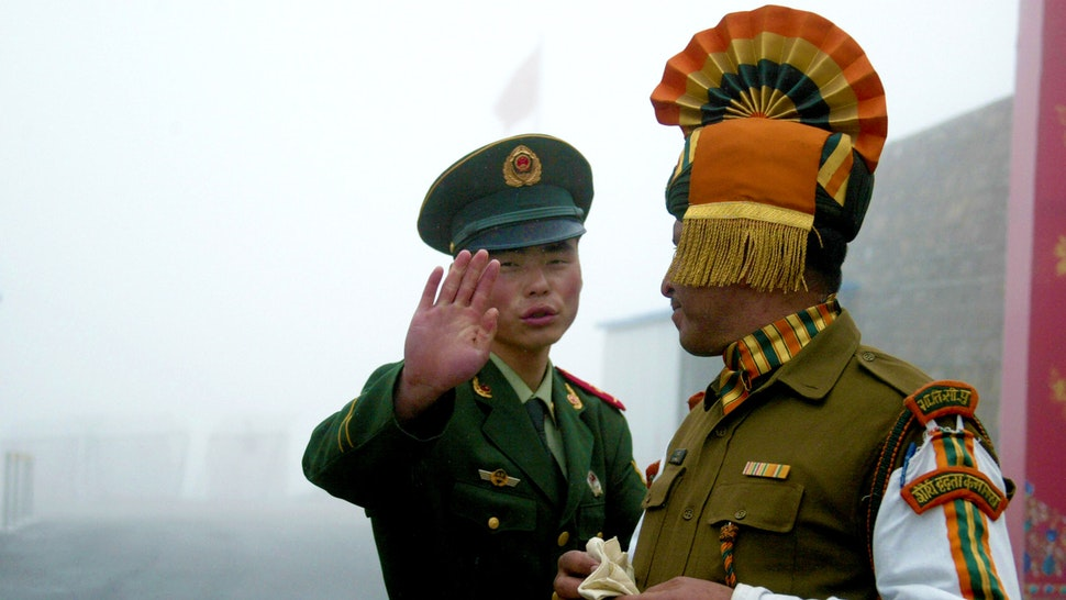In this photograph taken on July 10, 2008, A Chinese soldier gestures as he stands near an Indian soldier on the Chinese side of the ancient Nathu La border crossing between India and China. When the two Asian giants opened the 4,500-metre-high (15,000 feet) pass in 2006 to improve ties dogged by a bitter war in 1962 that saw the route closed for 44 years, many on both sides hoped it would boost trade. Two years on, optimism has given way to despair as the flow of traders has shrunk to a trickle because of red tape, poor facilities and sub-standard roads in India's remote northeastern mountainous state of Sikkim.