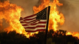 Flames approach an American flag at the Crown Fire on July 20, 2004 near Acton, California.