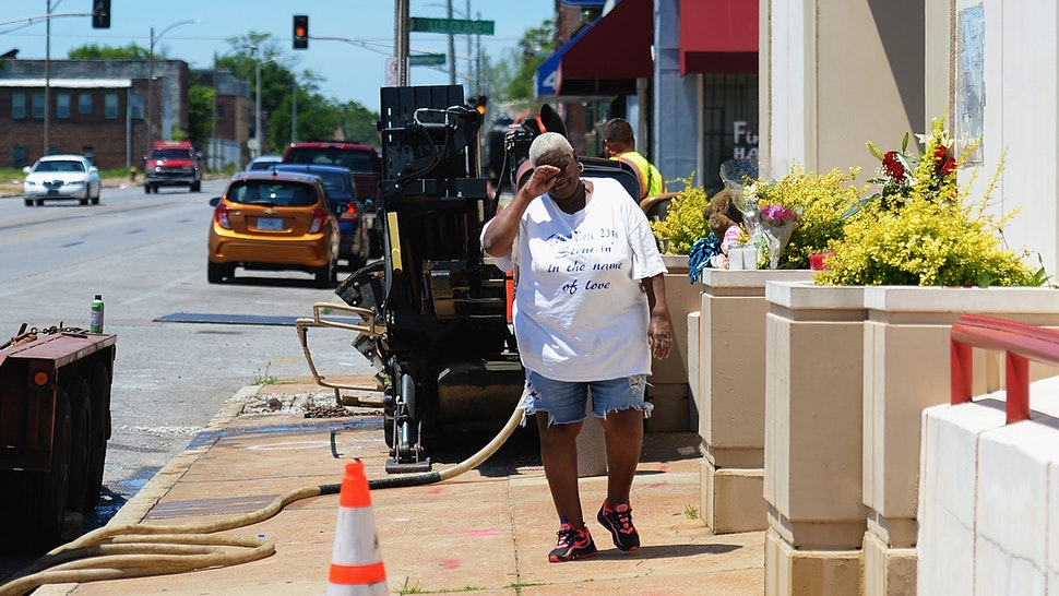 ST LOUIS, MO - JUNE 2: Diane Davis of St. Louis stops to leave flowers and pay respects to David Dorn, a 77-year-old retired police captain who was murdered during overnight rioting outside Lee's Pawn and Jewelry, on June 2, 2020 in St Louis, Missouri. Four police officers were reportedly shot in St. Louis overnight during violent clashes with protesters leading to looting and damage to local businesses.