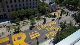 """People walk down 16th street after """"Defund The Police"""" was painted on the street near the White House on June 08, 2020 in Washington, DC. After days of protests in DC over the death of George Floyd, DC Mayor Muriel Bowser has renamed that section of 16th street """"Black Lives Matter Plaza"""". (Photo by Tasos Katopodis/Getty Images)"""