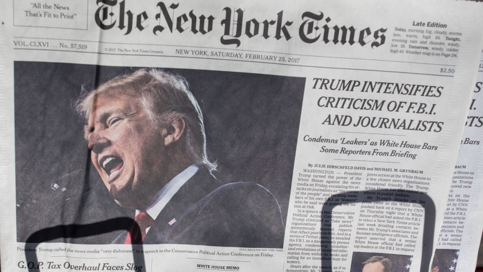 The front page of the New York Times carries a picture of President Donald Trump February 25, 2017 a day after he criticized in a speech the FBI and journalists in New York City. Certain media outlets were barred from attending a press briefing at the White House then day before. (Photo by Robert Nickelsberg/Getty Images)