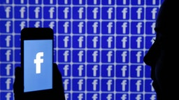 In this photo illustration, the Facebook logo is displayed on the screen of an iPhone in front of a TV screen displaying the Facebook logo on December 26, 2019 in Paris, France. The American company Facebook created in 2004 by Mark Zuckerberg builds technologies that give people the power to connect with friends and family, find communities and grow businesses. (Photo by Chesnot/Getty Images)