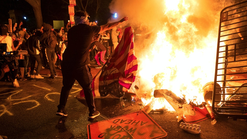 A protester throws a US flag into a burning barricade during a demonstration against the death of George Floyd near the White House on May 31, 2020 in Washington, DC. - Thousands of National Guard troops patrolled major US cities after five consecutive nights of protests over racism and police brutality that boiled over into arson and looting, sending shock waves through the country. The death Monday of an unarmed black man, George Floyd, at the hands of police in Minneapolis ignited this latest wave of outrage in the US over law enforcement's repeated use of lethal force against African Americans -- this one like others before captured on cellphone video.