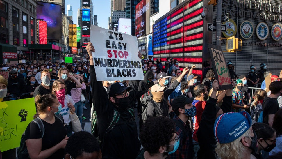 Black Lives Matter protesters kneel in Times Square during a march to honor George Floyd in Midtown Manhattan on May 31, 2020 in New York City. Protesters demonstrated for the fourth straight night after video emerged of a Minneapolis police officer, Derek Chauvin, pinning George Floyd's neck to the ground. Floyd was later pronounced dead while in police custody after being transported to Hennepin County Medical Center. The four officers involved have been fired and Chauvin has been arrested and charged with 3rd degree murder. (Photo by John Moore/Getty Images)
