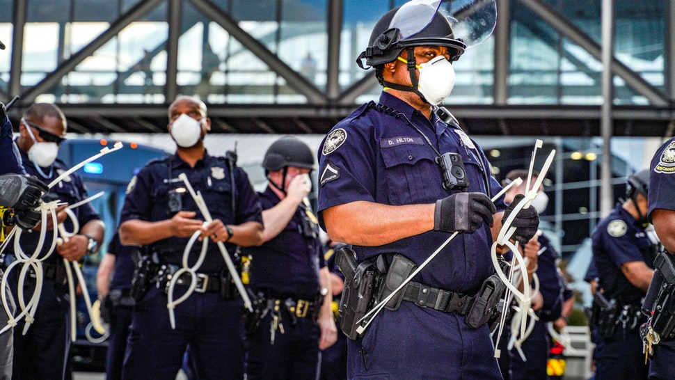 ATLANTA, USA - MAY 29: Police officers stand guard during a protest following the death of George Floyd outside of the CNN Center next to Centennial Olympic Park in downtown Atlanta, Georgia, United States on May 29, 2020. It was announced Friday that Derek Chauvin, the former Minneapolis police officer caught on camera with his knee on Floydâs neck, has been arrested and charged with third-degree murder and manslaughter.