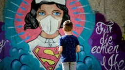 TOPSHOT - A boy stands in front of a graffiti painted by artist Kai 'Uzey' Wohlgemuth featuring a nurse as Superwoman on a wall in Hamm, western Germany, on April 8, 2020 refering to the spread of the novel coronavirus COVID-19.