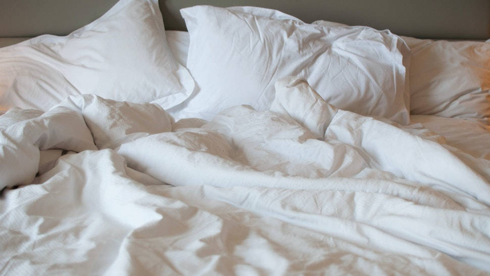 A close-up view of messy bed with comforter and pillows