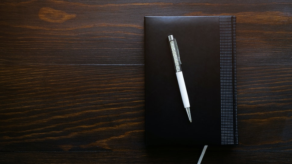 Pen, notebook or diary on a wooden table. Free space for text. The concept of office, education, business, making a plan for the day. Workplace businessman, entrepreneur or freelancer.